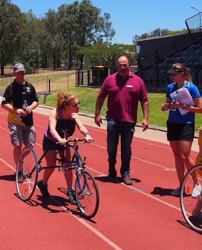Dr Sarah Reedman (QCPRRC Researcher), Richard Keith (Chairperson for RaceRunning Australia), Malcolm Davidson (Dejay Medical), working with athlete Tarsha on RaceRunning.